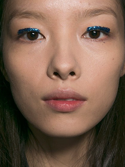 "The standout accessory has moved beyond shoes and bags. ""It's a little line of glitter — a makeup accessory,"" says makeup artist Peter Philips of the otherwise simple look at Dries Van Noten. ""No mascara. No lips. Just beautiful skin and the blue eyeliner."""